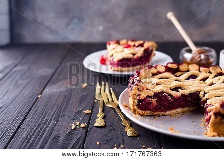 American homemade cherry pie on brown wooden background.