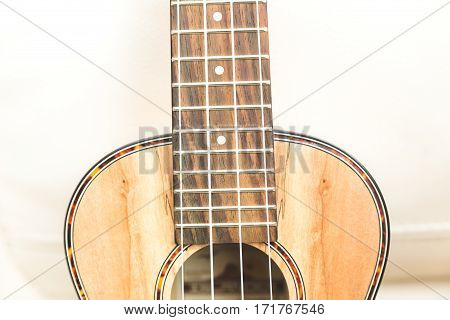 New upscale ukulele with four strings and unique textured wood grain finish.