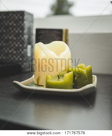 Large white candle and two smaller green candles on a plate on a shelf.