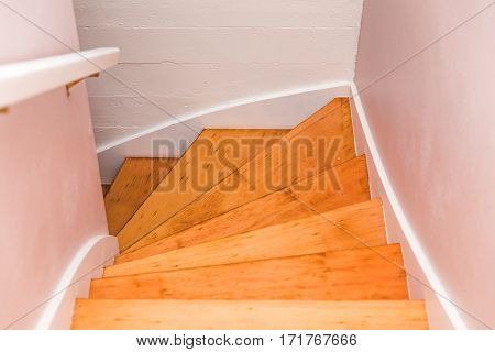 Wooden staircase or stairwell in modern home. Stairs are well-let from a skylight above.