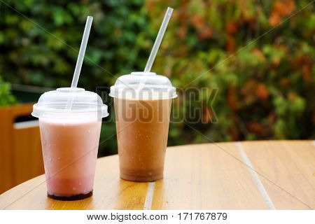 Plastic cups of delicious cool drinks on wooden table