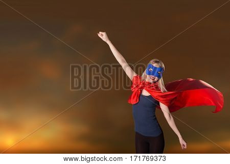 Female In Red Cape And Blue Mask On Sky Background, Sunset.