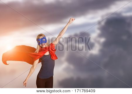 Female In Red Cape And Blue Mask On Sky Background, Sunlight.