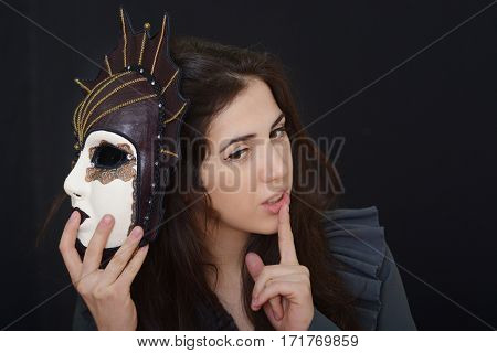 actress brunette holding an old theatrical mask in hands against a dark background