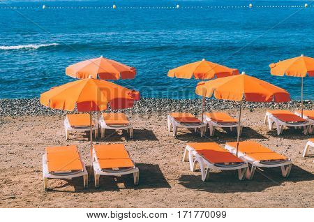 Orange sunshades and deckchairs against stony beach and ocean