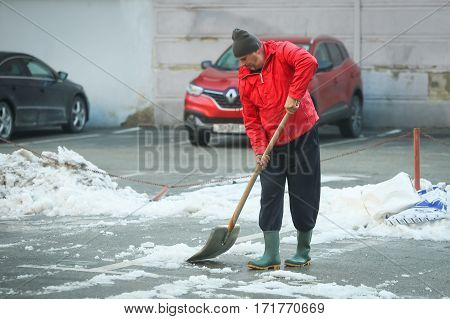 ZAGREB CROATIA - JANUARY 15 2017 : A man cleaning the snow off the parking lot with a shovel in Zagreb Croatia.