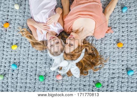 Top view of mother and child girl wearing rabbit ears and lying on floor