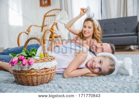 Happy family lying on the floor with basket full of Easter eggs and fresh tulips