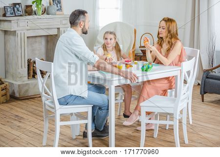 Happy young family sitting at table and painting Easter eggs together