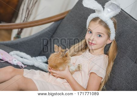 Little girl holding cute fluffy rabbit and smiling at camera