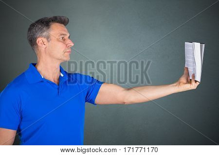 Longsighted Matured Man Reading Book While Stretching Hand On Gray Background