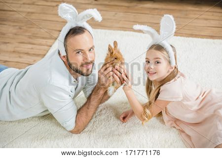 Father and daughter in bunny ears playing with rabbit and smiling at camera