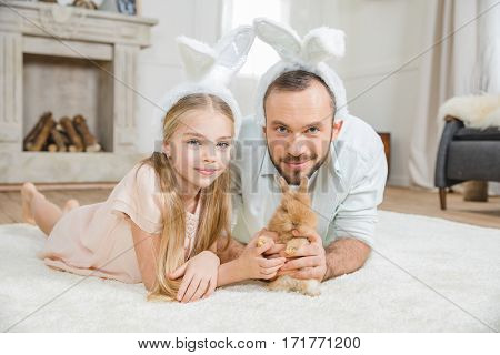 Happy father and daughter in bunny ears playing with rabbit at home