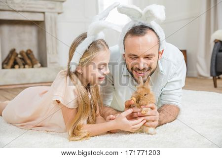 Happy father and daughter lying on carpet and playing with rabbit