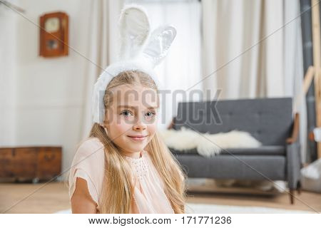 Beautiful little girl in bunny ears smiling at camera