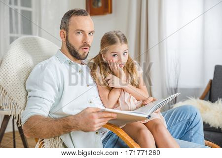Scared father and daughter sitting in rocking chair and reading book