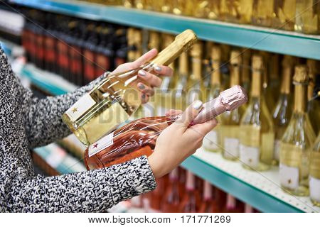 Woman With Bottles Of Rose And White Wine In Store