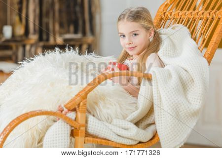 Cute girl holding cup while sitting under white blanket in rocking chair