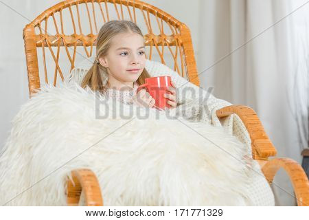 Cute little girl holding red cup while sitting in rocking chair