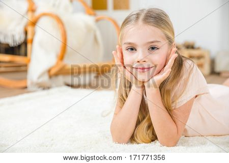 Cute little girl lying on white carpet and smiling at camera