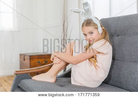 Cute girl in bunny ears sitting on grey sofa and smiling at camera