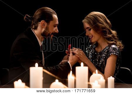 Smiling handsome man proposing to happy woman offering engagement ring on black