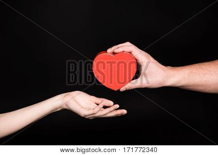 Partial view of man gives heart shaped present box to woman on black