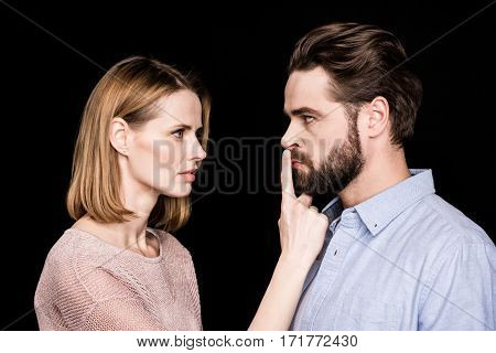 Young woman presses finger to mouth of displeased man on black