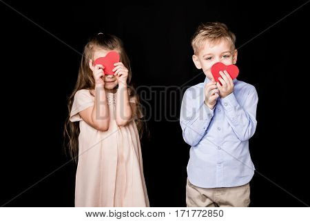Adorable little kids holding red paper hearts on black
