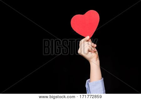 Close-up partial view of little boy holding red paper heart on black