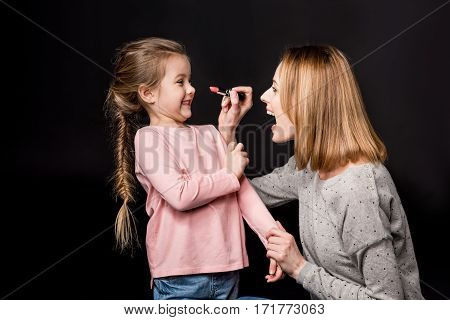 Excited mother trying to apply lipstick on smiling little daughter