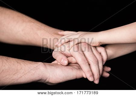 Close-up partial view of father and child stacking hands together on black