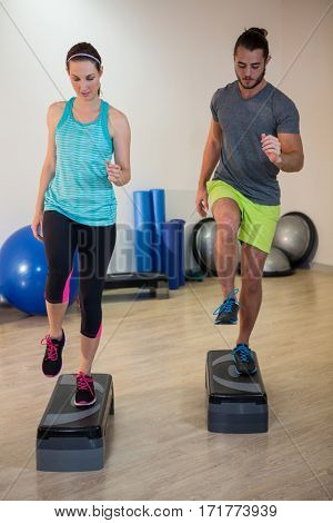 Man and woman doing step aerobic exercise on stepper in fitness studio
