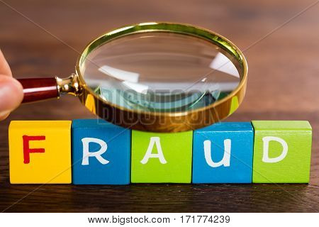 Person Hand With Magnifying Glass And The Word Fraud On Colorful Cubes