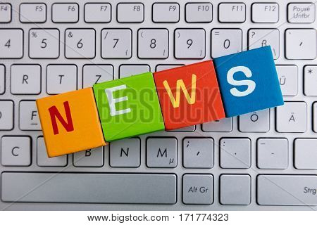News Text On Colorful Cubes Over Laptop Keyboard
