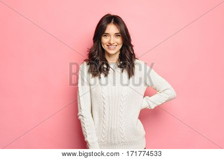 Young cheerful girl in winter white sweater over pink color background isolated