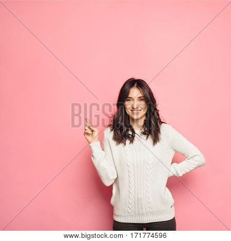 portrait of a happy casual woman wearing a white pullover pointing finger to the left isolated on pink color background