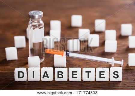 The Word Diabetes With Insulin And Syringe On Wooden Desk