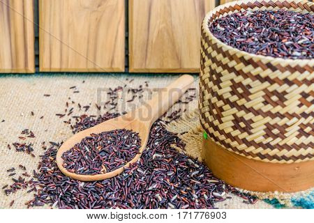 Hom Nil (black jasmine rice) in kratip and wooden spoon on sack wooden background