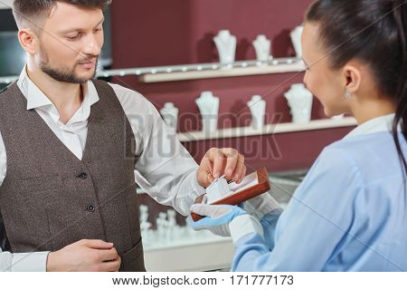 Helping to choose. Young man taking an engagement ring professional jeweler is showing him man buying jewelry at the store consumerism customer people sale discount shopping luxury fiance concept
