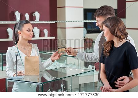 Using his credit card. Cheerful young man giving his credit card to the shop assistant while buying jewelry with his beautiful happy girlfriend sale consumerism banking people love couple concept
