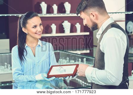 Friendly assistance. Beautiful young female jeweler smiling cheerfully showing a diamond ring to her male customer at the store wedding bridal jewelry buying shopping sale consumerism client customer