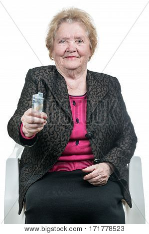 Old woman sitting on a chair offers money keeping them at arm length, isolated on white background