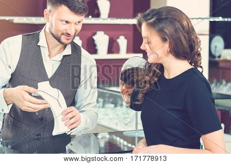Professional advice. Beautiful young cheerful woman buying a necklace from a professional jeweler at the local boutique shopping shopaholic consumerism choosing buyer spending money femininity concept
