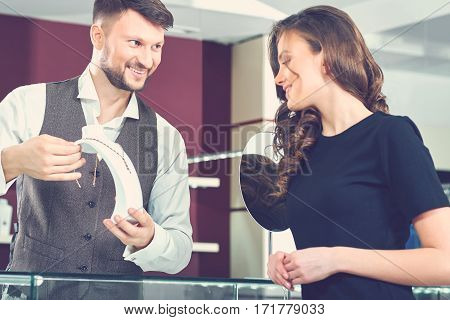 Only the best for his clients. Cheerful professional male jeweler smiling working with his female customer woman buying jewelry concept salesman seller sale discount offer shopping spending consumer