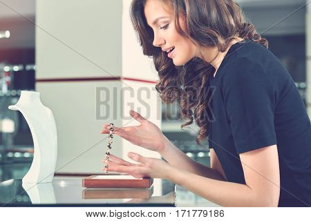 I need this necklace Toned shot of a beautiful excited woman examining a precious necklace at the jewelry store shopaholic lifestyle present gift spending sale offer discount consumerism concept .