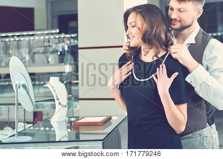 Looking magnificent. Handsome young man helping his beautiful girlfriend trying on pearl necklace at the jewelry store copyspace emotions love affection anniversary togetherness couples toned concept