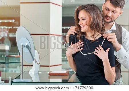 You look gorgeous Happy young couple trying on a pearl necklace at the jewelry store cpyspace anniversary sale shopping buying consumerism wealthy wellbeing people customers love couple concept.