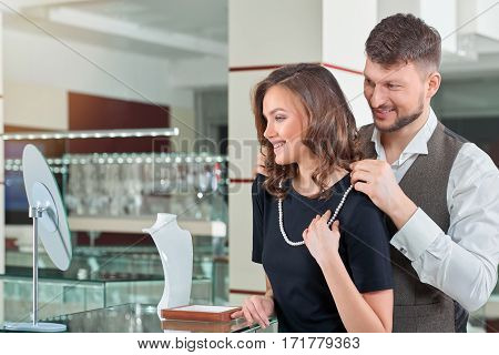 Buying her jewelry. Handsome loving man putting a pearl necklace on the neck of his beautiful happy girlfriend couple buying jewelry at the jewelry store love consumerism sale luxury concept copyspace