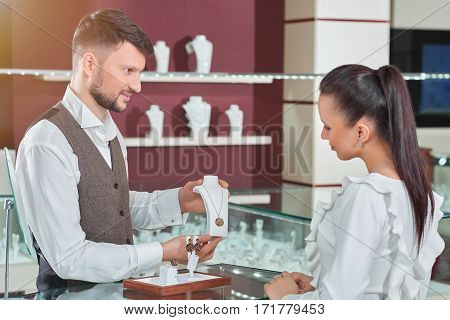 Treating herself. Cheerful dark haired female customer examining a necklace professional jeweler is showing her consumerism people shopping buyer shopper money luxury wellbeing profession concept